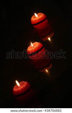 An abstract of three round candles lighting in the dark.