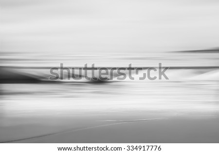 An abstract seascape in black and white made with a long exposure and panning motion. - stock photo