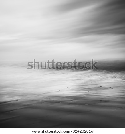 An abstract seascape rendered in black and white.  Image made using a long exposure and panning movement for a soft, blurred effect.