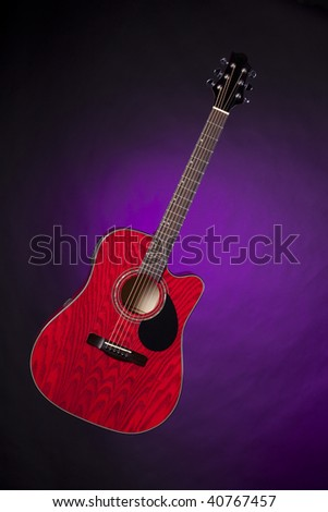 An acoustic electric red finish guitar isolated against a spotlight purple background in the vertical format.