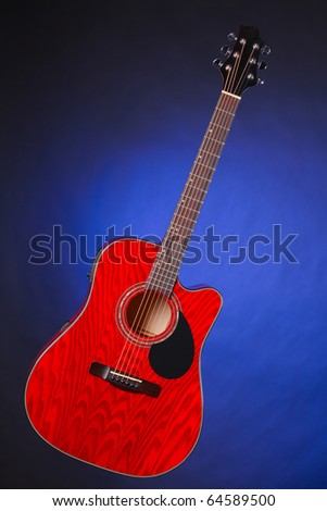 An acoustic electric red wood guitar isolated against a spotlight blue background.