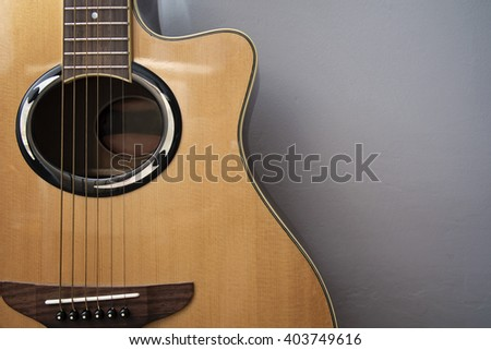 An acoustic guitar in front of grey wall