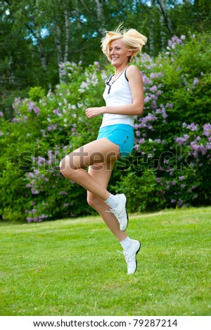 An active beautiful caucasian woman jumping in the park - stock photo