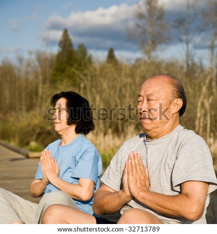 An active senior asian couple exercises and practices yoga and meditation - stock photo