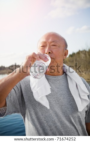 An active senior asian man drinking water after exercise - stock photo