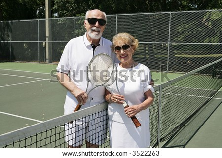 An active senior couple in sunglasses getting ready to play tennis. - stock photo