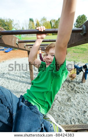 An active young boy playing on a school playground.