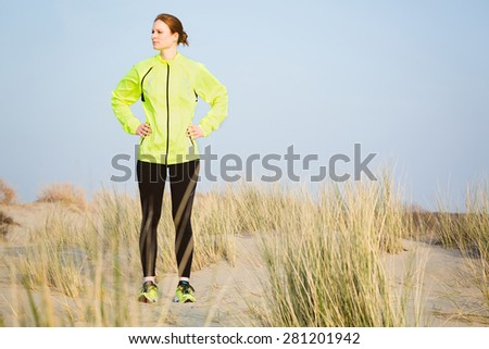 An active young woman wearing sport clothing stands on a beach with dunes and looks to her side.