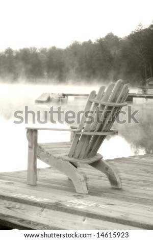An Adirondack chair sits on a dock in Old Forgr, NY.  Softened and dreamy. - stock photo