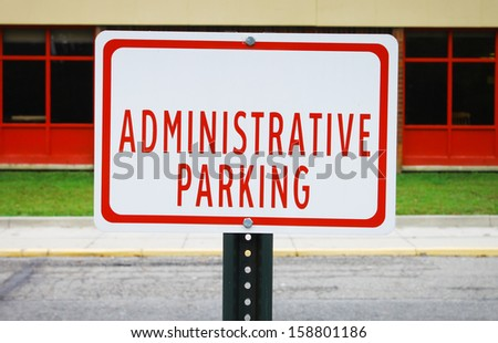 An Administrative parking sign in front of a windowed building along the street and sidewalk - stock photo