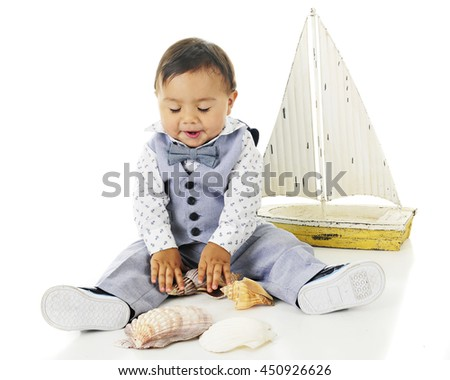 An adorable baby boy happily looking down at the sea shells he's playing with.  A toy sailboat is nearby.  On a white background.
