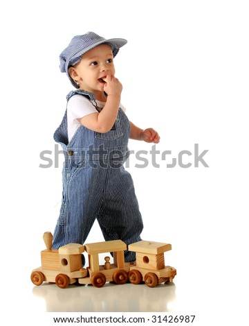 An adorable baby boy in engineer's garb chewing on a wooden passenger from his toy train.  Isolated on white. - stock photo