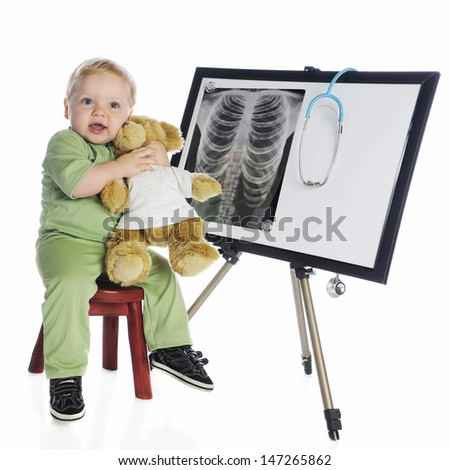 An adorable baby boy in green scrubs hugging his toy bear as he sits by an easel displaying a human chest x-ray.  On a white background. - stock photo