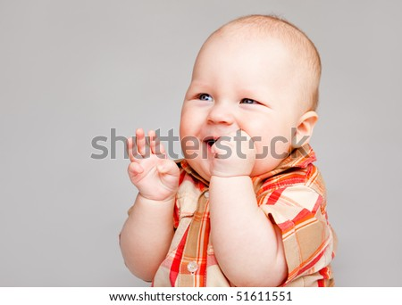 An adorable baby boy laughing, on a gray background - stock photo