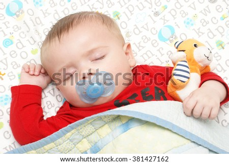 An adorable baby boy of five months is dreaming away during his peaceful sleep in his crib. - stock photo