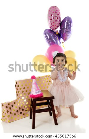 An adorable baby girl eating the #1 candle from her first birthday cake.  On a white background. - stock photo
