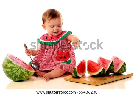 An adorable baby girl going for a slice of juicy watermelon.  Isolated on white. - stock photo
