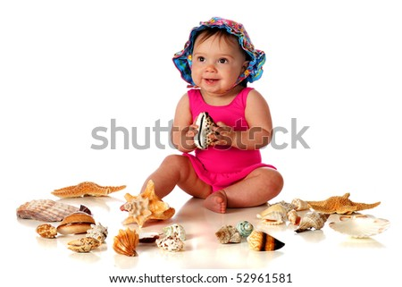 An adorable baby girl in her swimsuit and sunhat happily holding one of a variety of sea shells. Isolated on white. - stock photo