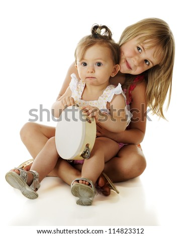 An adorable baby girl sitting on her happy elementary-aged sister's lap.  On a white background.
