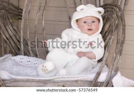 An adorable baby with blue eyes, wearing a bear suit, sits in a rustic chair. - stock photo