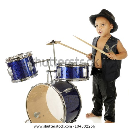 An adorable, barefoot preschooler dressed as a rock star, beating on a drum set.  On a white background.  Motion blur on the drum sticks. - stock photo
