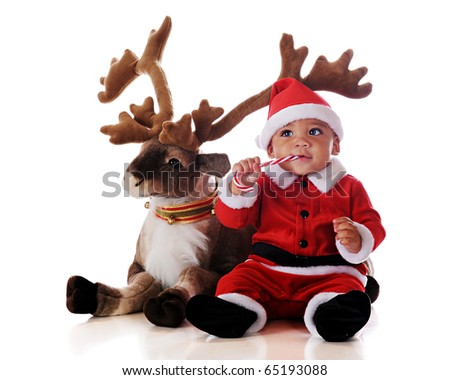 An adorable biracial Santa eating a candy cane by his reindeer.  Isolated on white. - stock photo