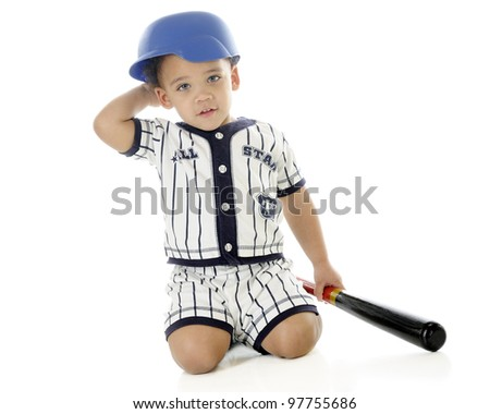 An adorable biracial 2-year-old clutching a bat while in his baseball uniform and helmet.  On a white background. - stock photo