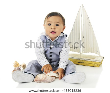 An adorable, dressed up baby boy playing with sea shells in front of his toy sailboat.  On a white background. - stock photo