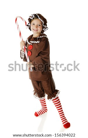 """An adorable elementary """"gingerbread cookie"""" holding a large candy cane.  On a white background. - stock photo"""