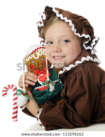"""An adorable elementary """"gingerbread girl"""" hugging her gingerbread girl doll.  On a white background. - stock photo"""