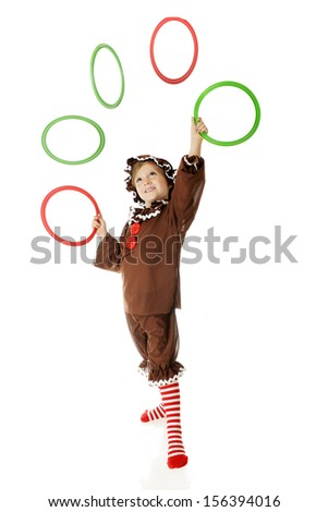 "An adorable elementary ""gingerbread girl"" juggling Christmas colored rings.  (Motion blur on airborne rings.)  On a white background."