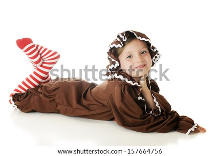 """an adorable elementary """"gingerbread girl"""" reclined on her belly with her head propped up by her hand and striped legs crossed behind.  On a white background. - stock photo"""