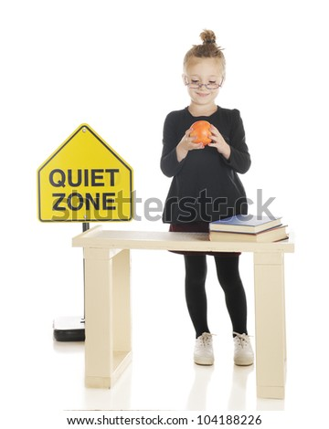 An adorable girl playing teacher.  She's admiring an apple as she stands behind her desk.  On a white background. - stock photo