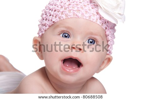 An adorable image of a cute baby who has her mouth open with excitement.  She is wearing a pink headband with a white bow. - stock photo