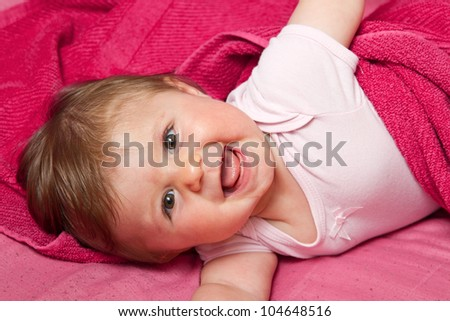 An adorable, laughing baby looking at camera - stock photo