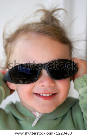 An adorable laughing 2 year old laughs as she playfully tries on a pair of sunglasses. - stock photo