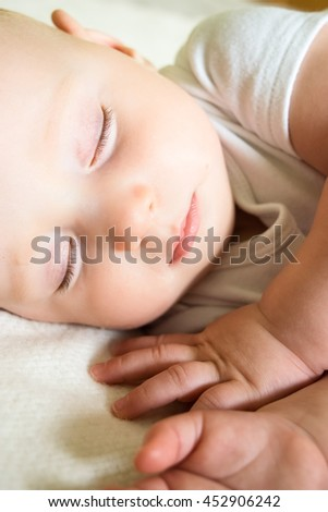 An adorable little baby is sleeping on the bed in a white clothes