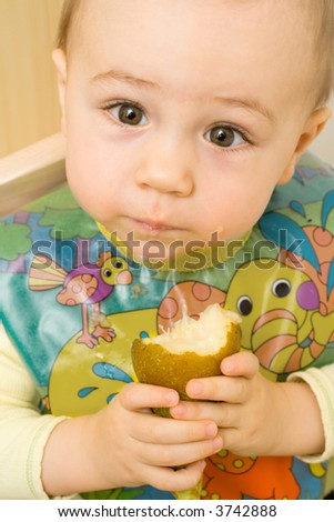 An adorable little baby with big brown eyes, wearing a colorful bib and eating a fresh pear.