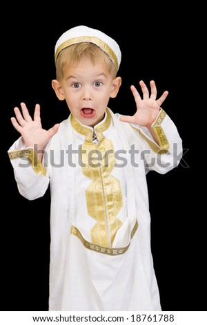 An adorable little boy dressed in Arabian thobe, isolated on black.