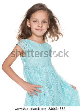 An adorable little girl in a blue dress is standing against the white background - stock photo