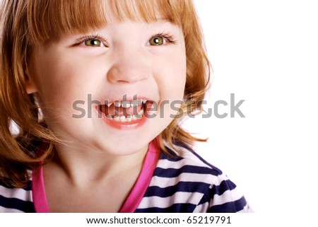 An adorable little girl laughing in front of a white background. - stock photo