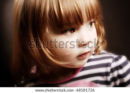 An adorable little girl looking to the light in front of a black background.