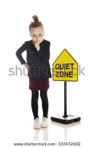 """An adorable little girl school teacher or librarian, gesturing to silence the viewer.  She stands in front of a """"Quiet Zone"""" sign.  On a white background. - stock photo"""