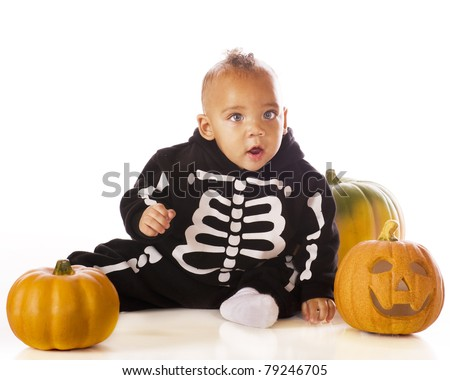An adorable mixed race baby boy dressed as a skeleton for Halloween.  He's sitting among 3 pumpkins.  Isolated on white. - stock photo