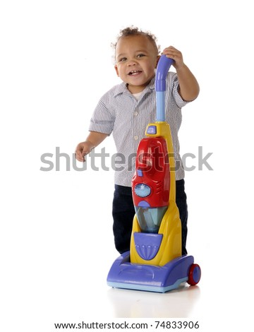 An adorable mixed race toddler showing off his toy upright vacuum cleaner.  Isolated on white. - stock photo