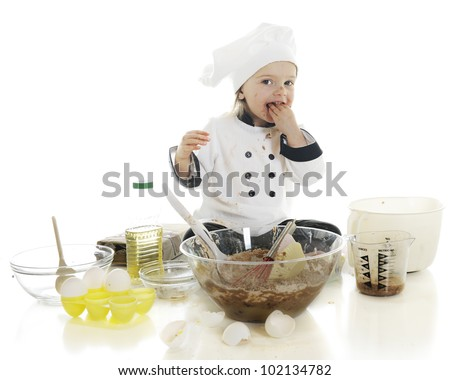 "An adorable preschool ""chef"" tasting a fistful of the chocolate cake batter that she's been making.  On a white background. - stock photo"