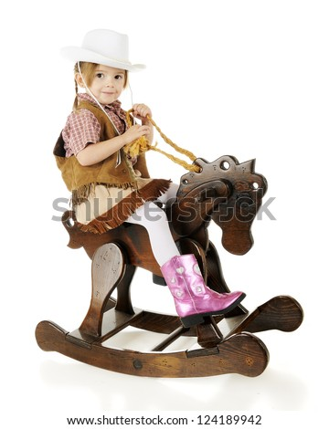 An adorable preschool cowgirl happily riding her wooden rocking horse.  On a white background. - stock photo