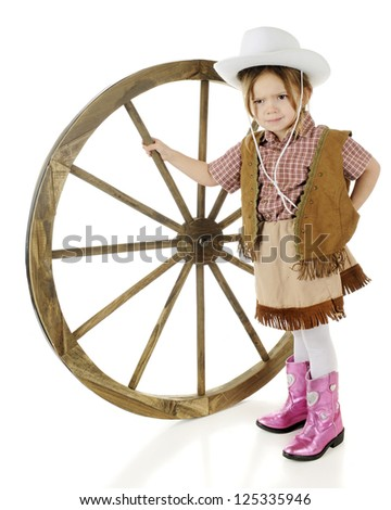 An adorable preschool cowgirl looking mad as she stands propping up a large wooden wagon wheel.  On a white background. - stock photo