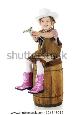 An adorable preschool cowgirl pointing her gun while sitting on a rustic old barrel.  On a white background. - stock photo