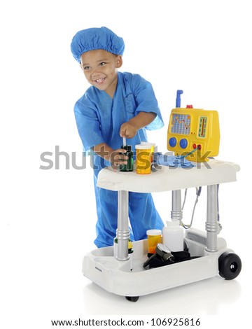 "An adorable preschool ""doctor"" happily drawing up medicine from his emergency cart.  On a white background."